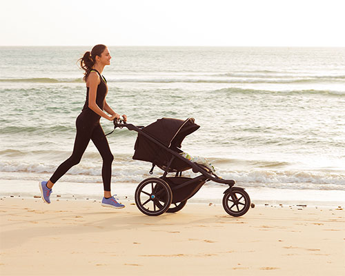 Mom running on the beach with stroller